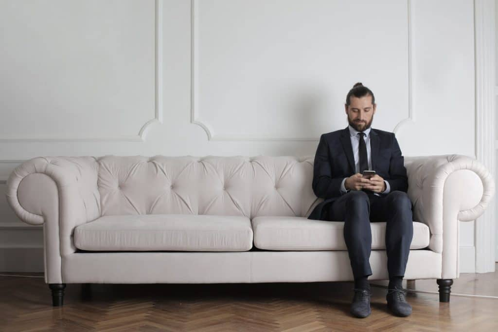 man working on smartphone on white couch
